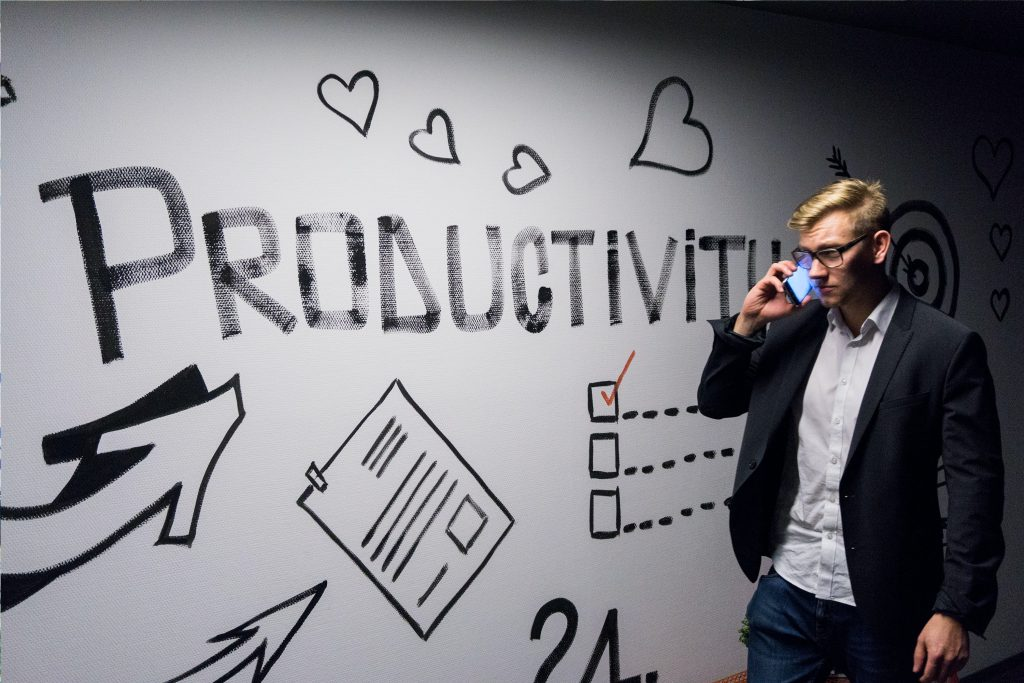 man holding smartphone looking at productivity wall decor