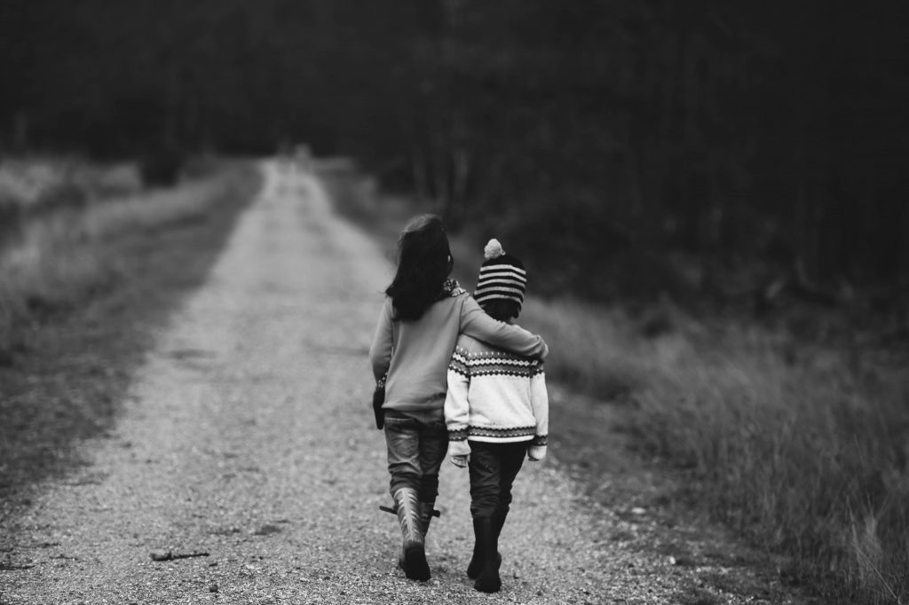 grayscale photography of kids walking on road