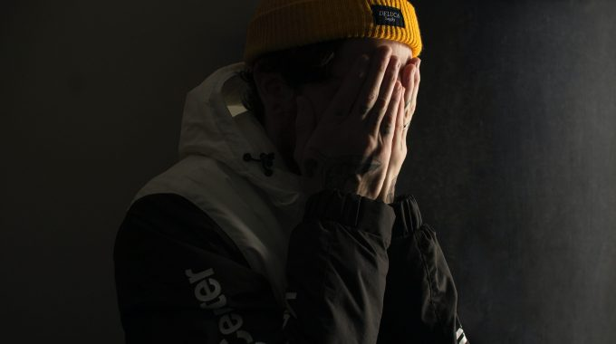 Man Covering His Face With Both Hands
