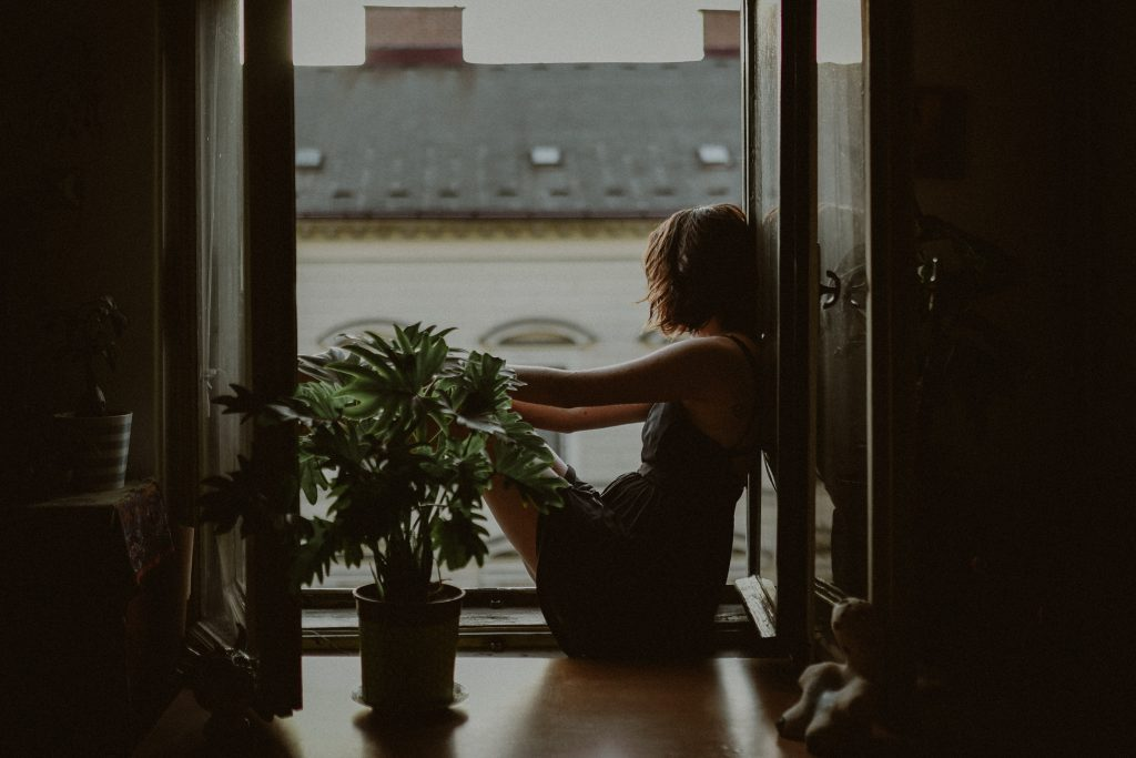 woman leaning on door looking outside